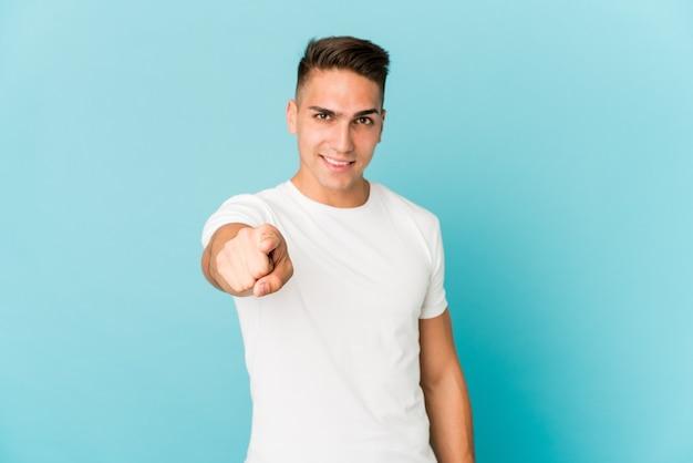 Młody przystojny mężczyzna kaukaski na białym tle wesoły uśmiech wskazujący na przód.