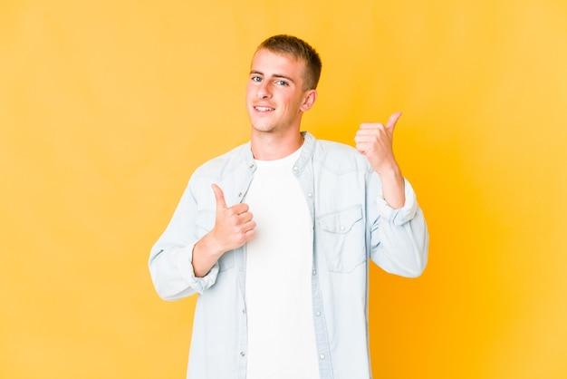 Młody przystojny mężczyzna kaukaski podnosząc kciuki do góry, uśmiechnięty i pewny siebie.