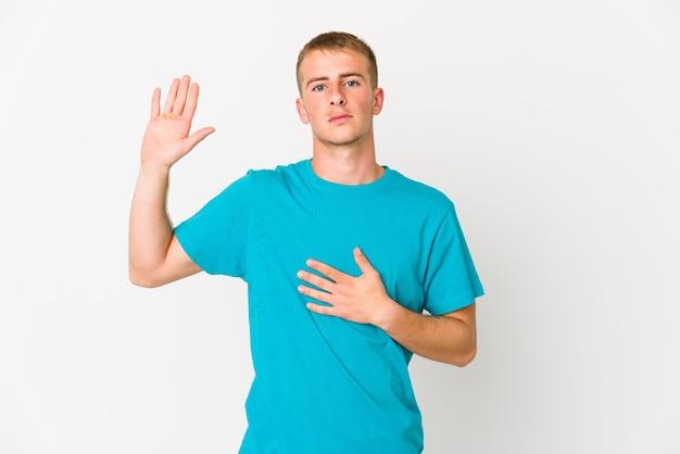 Młody przystojny mężczyzna kaukaski składając przysięgę, kładąc rękę na piersi.