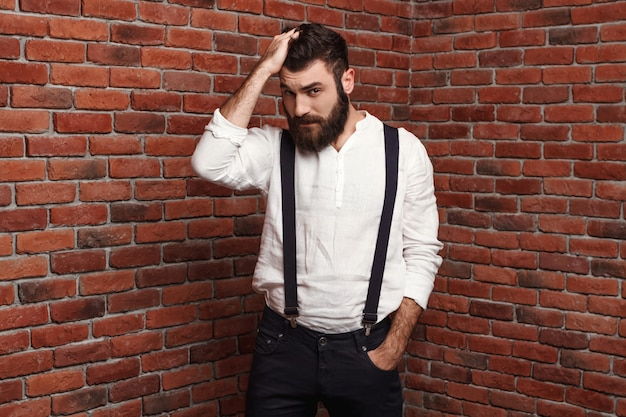 Młody przystojny mężczyzna koryguje fryzurę na ściana z cegieł.
