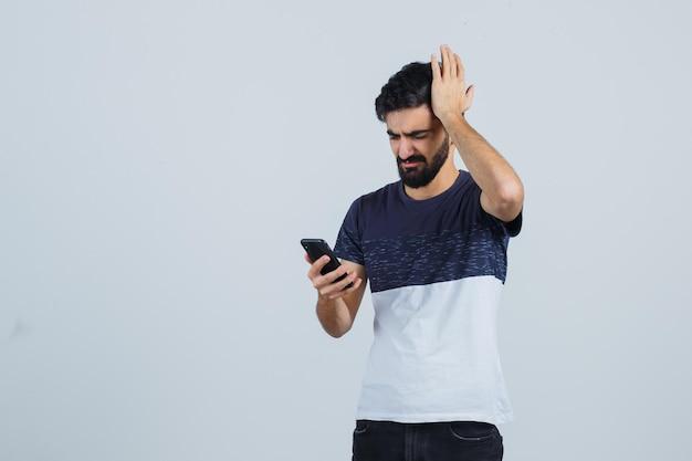 Młody przystojny mężczyzna korzystający z telefonu