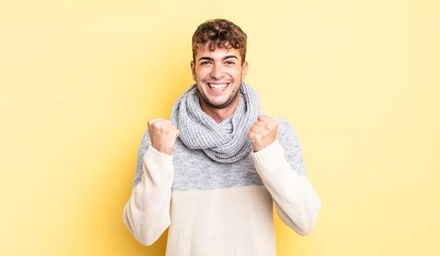 Młody przystojny mężczyzna krzycząc triumfalnie, śmiejąc się i czując się szczęśliwy i podekscytowany podczas świętowania sukcesu