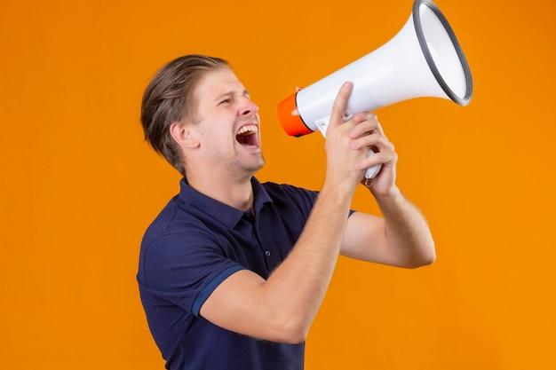 Młody przystojny mężczyzna krzyczący przez megafon wyszedł i zaskoczony, stojąc na pomarańczowym tle