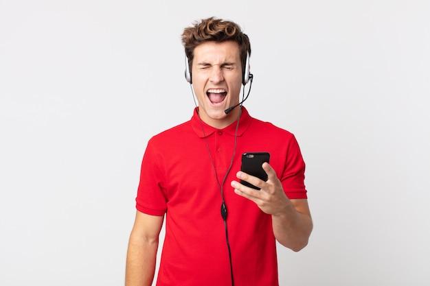 Młody przystojny mężczyzna krzyczy agresywnie, wygląda na bardzo zły ze smartfonem i zestawem słuchawkowym
