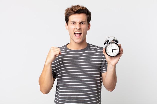 Młody przystojny mężczyzna krzyczy agresywnie z gniewnym wyrazem twarzy i trzyma budzik