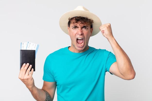 Młody przystojny mężczyzna krzyczy agresywnie z gniewnym wyrazem twarzy. podróżnik trzymający paszport