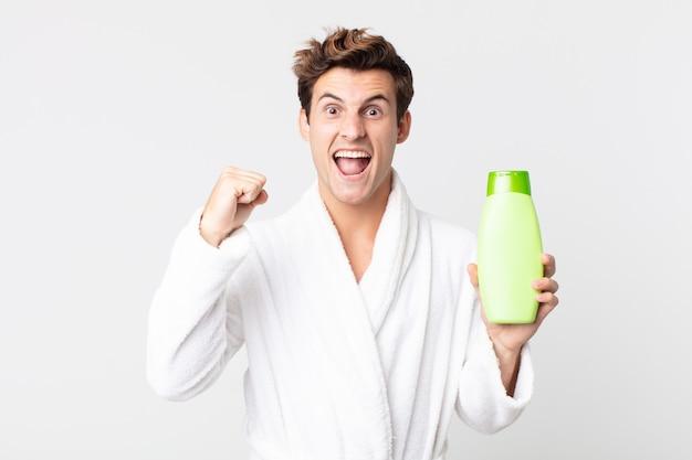Młody przystojny mężczyzna krzyczy agresywnie z gniewnym wyrazem twarzy w szlafroku i trzyma butelkę szamponu