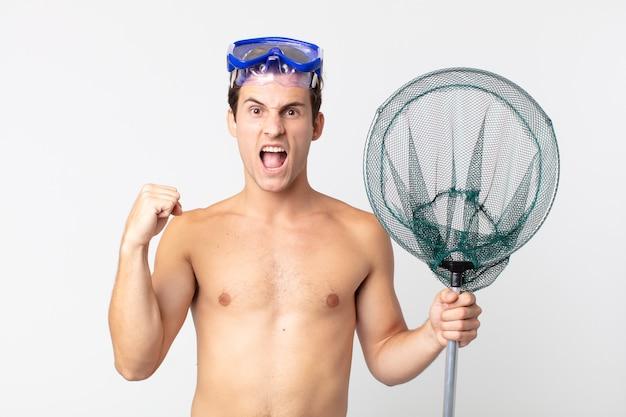 Młody przystojny mężczyzna krzyczy agresywnie z gniewnym wyrazem twarzy z goglami i siecią rybacką