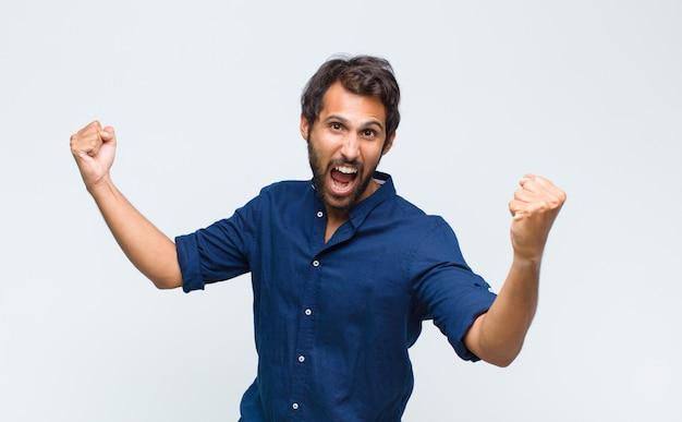 Młody przystojny mężczyzna krzyczy triumfalnie, wyglądając jak podekscytowany, szczęśliwy i zaskoczony zwycięzca, świętuje