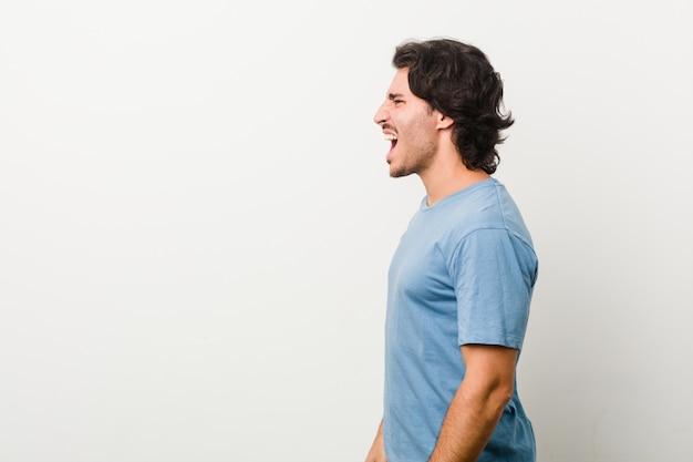 Młody przystojny mężczyzna krzyczy w kierunku białej przestrzeni przeciw białej ścianie