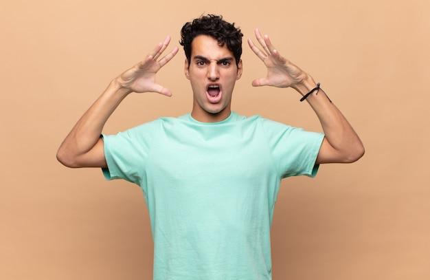 Młody przystojny mężczyzna krzyczy z rękami do góry, czuje się wściekły, sfrustrowany, zestresowany i zdenerwowany