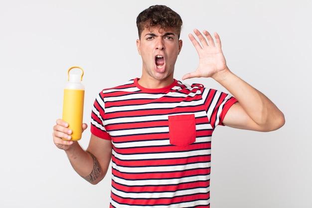 Młody przystojny mężczyzna krzyczy z rękami w górze i trzyma termos z kawą