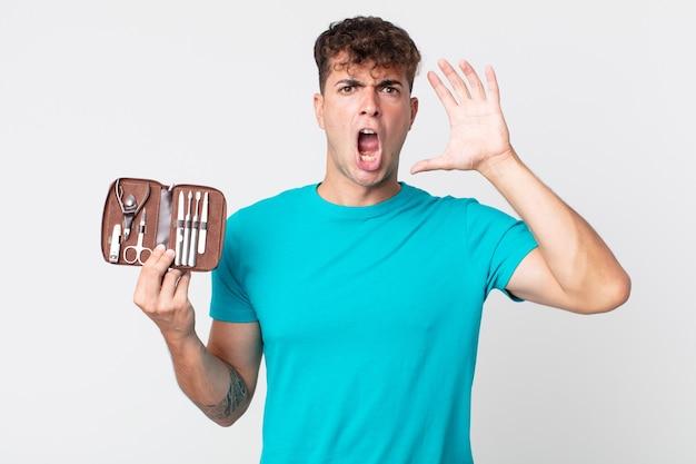 Młody przystojny mężczyzna krzyczy z rękami w górze i trzyma walizkę z narzędziami do paznokci