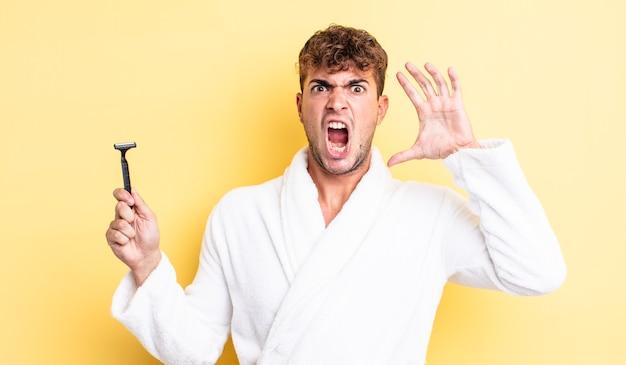 Młody przystojny mężczyzna krzyczy z rękami w powietrzu. koncepcja golenia