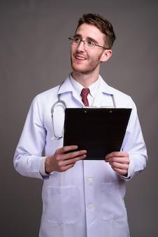 Młody przystojny mężczyzna lekarz noszenie okularów przeciwko szarości
