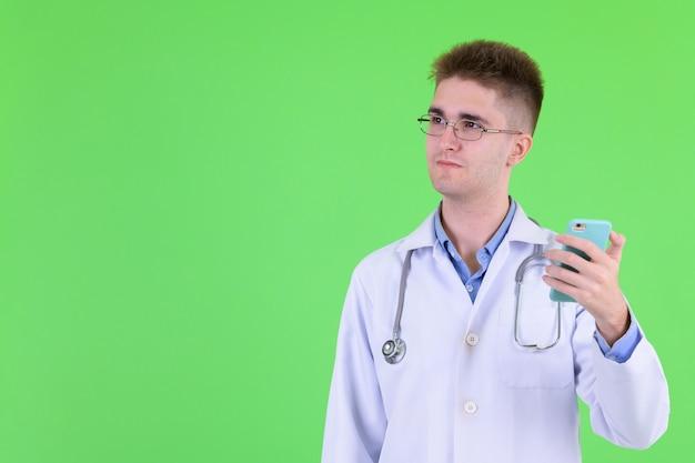 Młody przystojny mężczyzna lekarz z okularami przeciwko klucz chrominancji z zieloną ścianą