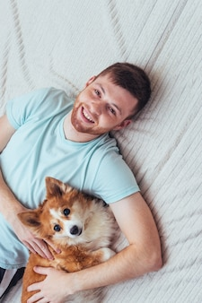 Młody przystojny mężczyzna leży w objęciach z rudym psem.