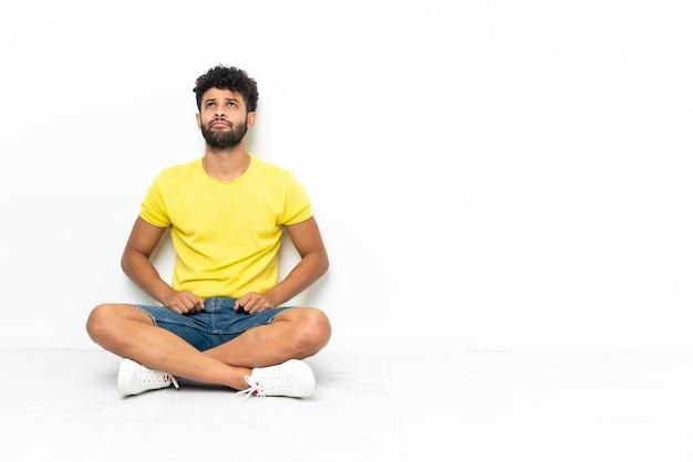 Młody przystojny mężczyzna marokański siedzi na podłodze na białym tle i patrząc w górę