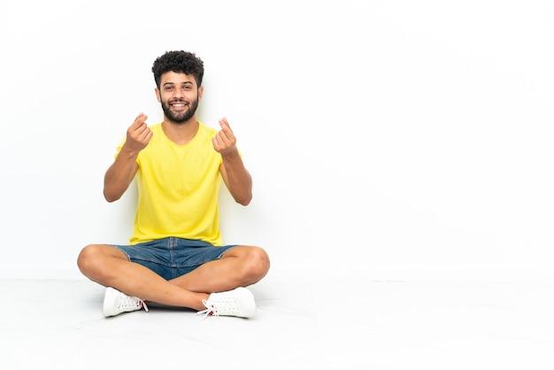 Młody przystojny mężczyzna marokański siedzi na podłodze na białym tle, zarabiać pieniądze gestem