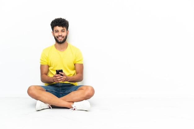 Młody przystojny mężczyzna marokański siedzi na podłodze na białym tle