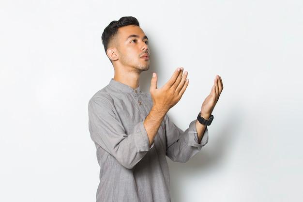 Młody przystojny mężczyzna modlący się na białym tle