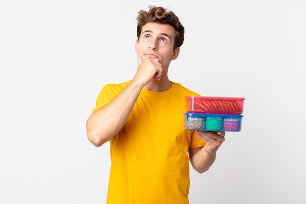 Młody przystojny mężczyzna myślący, mający wątpliwości i zdezorientowany, trzymający pudełka na lunch