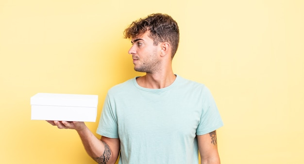 Młody przystojny mężczyzna myślący, wyobrażający sobie lub marzący o widoku profilu. koncepcja białego pudełka