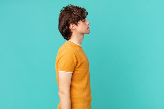 Młody przystojny mężczyzna myślący, wyobrażający sobie lub marzący o widoku profilu