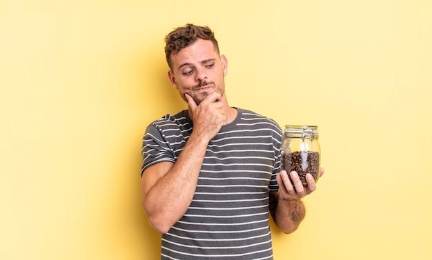 Młody przystojny mężczyzna myśli, czuje wątpliwości i jest zdezorientowany pojęciem ziaren kawy