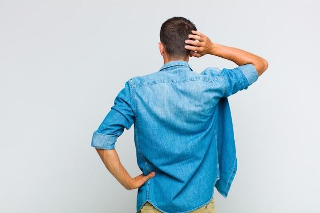 Młody przystojny mężczyzna myśli lub wątpi, drapie się po głowie, czuje się zdziwiony i zdezorientowany, widok z tyłu lub z tyłu