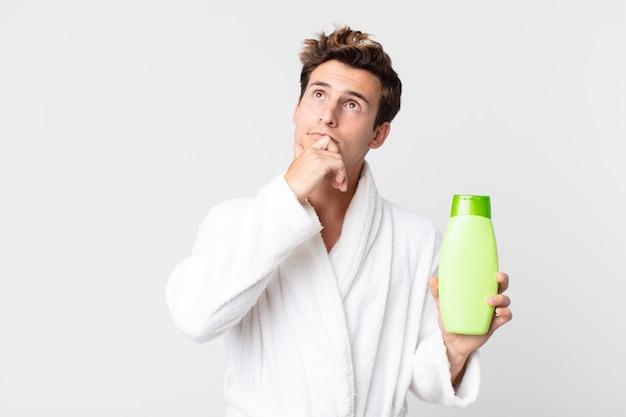 Młody przystojny mężczyzna myśli, wątpi i myli się ze szlafrokiem i trzyma butelkę szamponu
