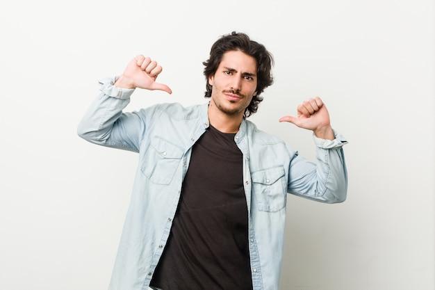 Młody przystojny mężczyzna na białej ścianie czuje się dumny i pewny siebie
