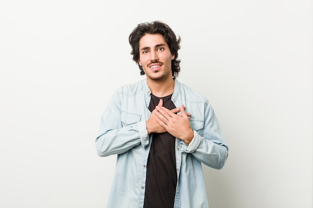 Młody przystojny mężczyzna na białej ścianie ma przyjazny wyraz, przyciskając dłoń do klatki piersiowej.