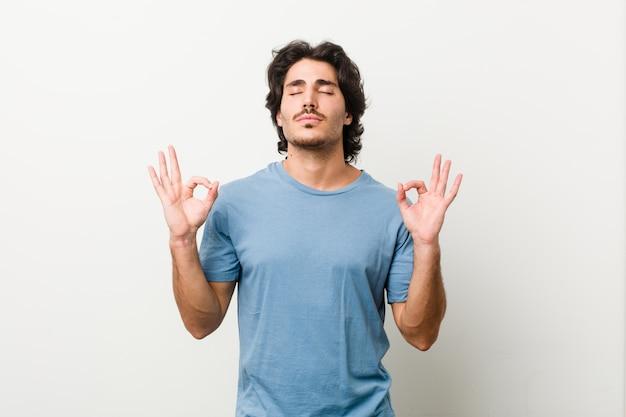 Młody przystojny mężczyzna na białej ścianie relaksuje po ciężkim dniu pracy, wykonuje jogi.