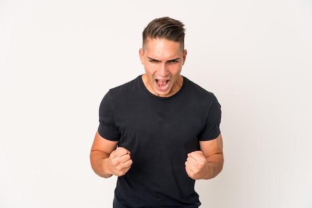 Młody przystojny mężczyzna na białym tle krzycząc bardzo zły, pojęcie wściekłości, sfrustrowany