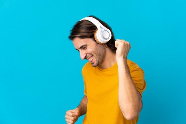 Młody przystojny mężczyzna na białym tle na niebieskiej ścianie, słuchanie muzyki i taniec