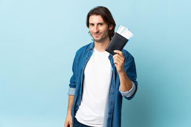 Młody przystojny mężczyzna na białym tle na niebieskiej ścianie szczęśliwy na wakacjach z biletami paszportowymi i lotniczymi