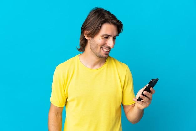 Młody przystojny mężczyzna na białym tle na niebieskiej ścianie, wysyłając wiadomość lub e-mail z telefonu komórkowego