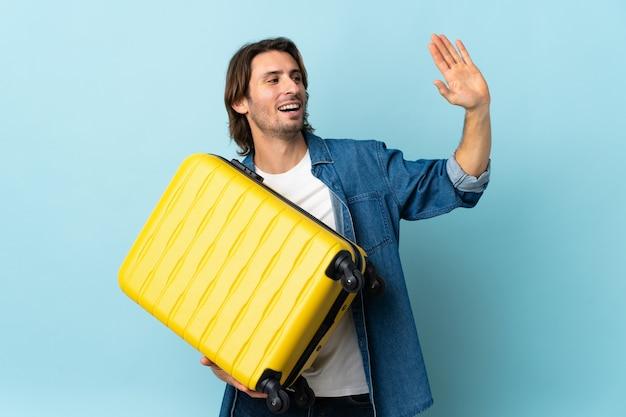 Młody przystojny mężczyzna na białym tle na niebieskim tle w wakacje z walizką podróżną i pozdrawiając