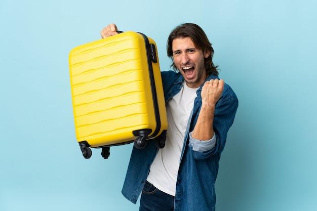Młody przystojny mężczyzna na białym tle na niebieskim tle w wakacje z walizką podróżną
