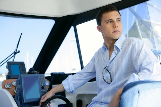 Młody przystojny mężczyzna na jachtu łodzi wnętrzu