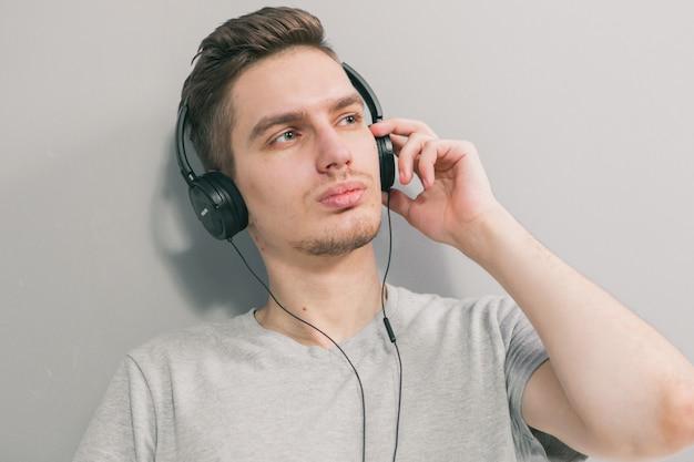 Młody przystojny mężczyzna na kanapie, słuchając muzyki. zostań w domu