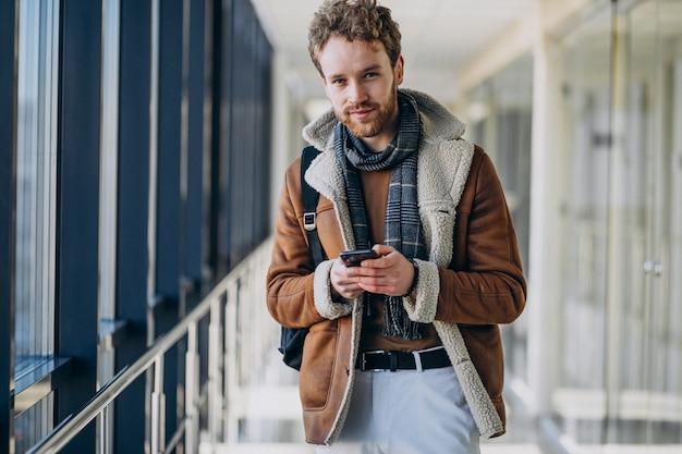 Młody przystojny mężczyzna na lotnisku rozmawia przez telefon