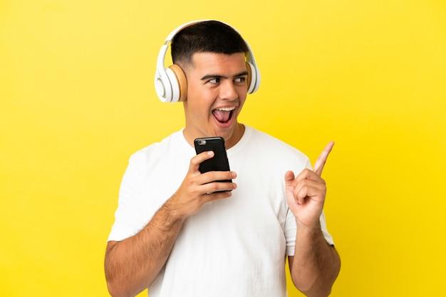 Młody przystojny mężczyzna na odosobnionym żółtym tle słuchania muzyki za pomocą telefonu komórkowego i śpiewania