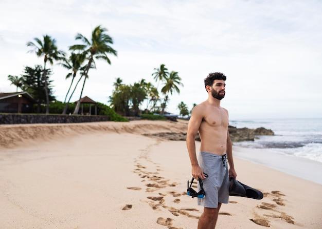 Młody przystojny mężczyzna na plaży ze sprzętem do nurkowania