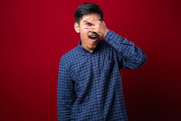 Młody przystojny mężczyzna na pojedyncze czerwone tło zerkając w szoku zasłaniając twarz i oczy ręką, patrząc przez palce z zakłopotanym wyrazem twarzy.