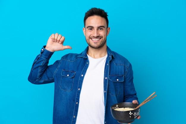 Młody przystojny mężczyzna na pojedyncze niebieskie ściany dumny i zadowolony z siebie, trzymając miskę makaronu pałeczkami