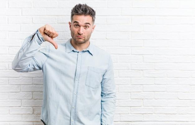 Młody przystojny mężczyzna na ścianie z cegieł, pokazując gest niechęci, kciuki w dół.