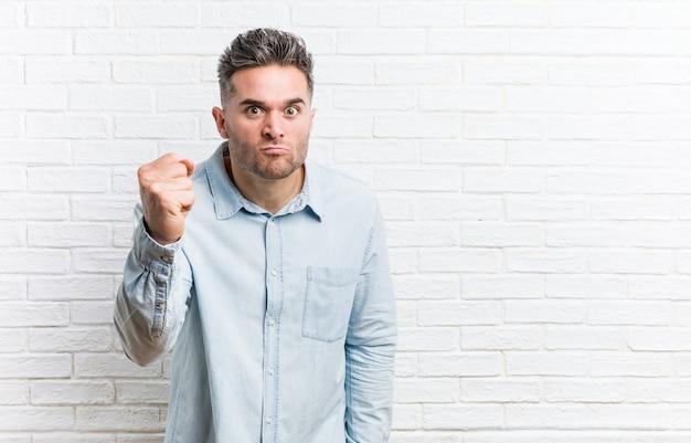 Młody przystojny mężczyzna na ścianie z cegieł pokazując pięść do kamery, agresywny wyraz twarzy.