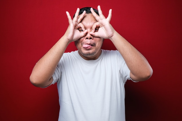 Młody przystojny mężczyzna na sobie biały t-shirt robi ok gest jak lornetka wystaje język, oczy patrząc przez palce. szalona ekspresja na czerwonym tle